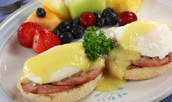 Eggs Benedict on a plate with fresh fruit